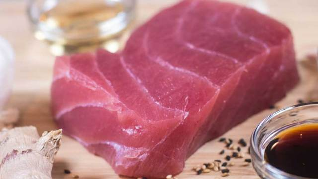 raw tuna steak with ginger, soy, and sesame seeds.