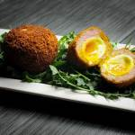 Scotch Eggs sliced open on a plate of arugula.