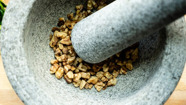 Toasted walnuts being ground in a mortar and pestle