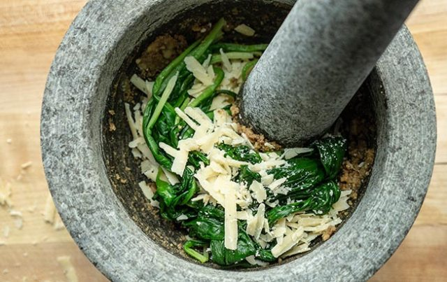 Pesto ingredients being crushed and ground in a mortar and pestle.