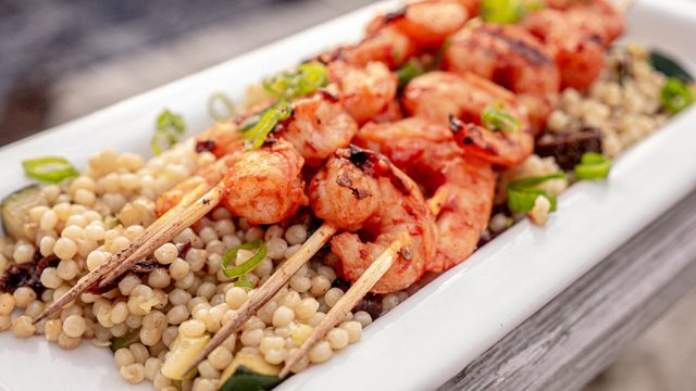 Perfectly grilled shrimp on a plate of couscous