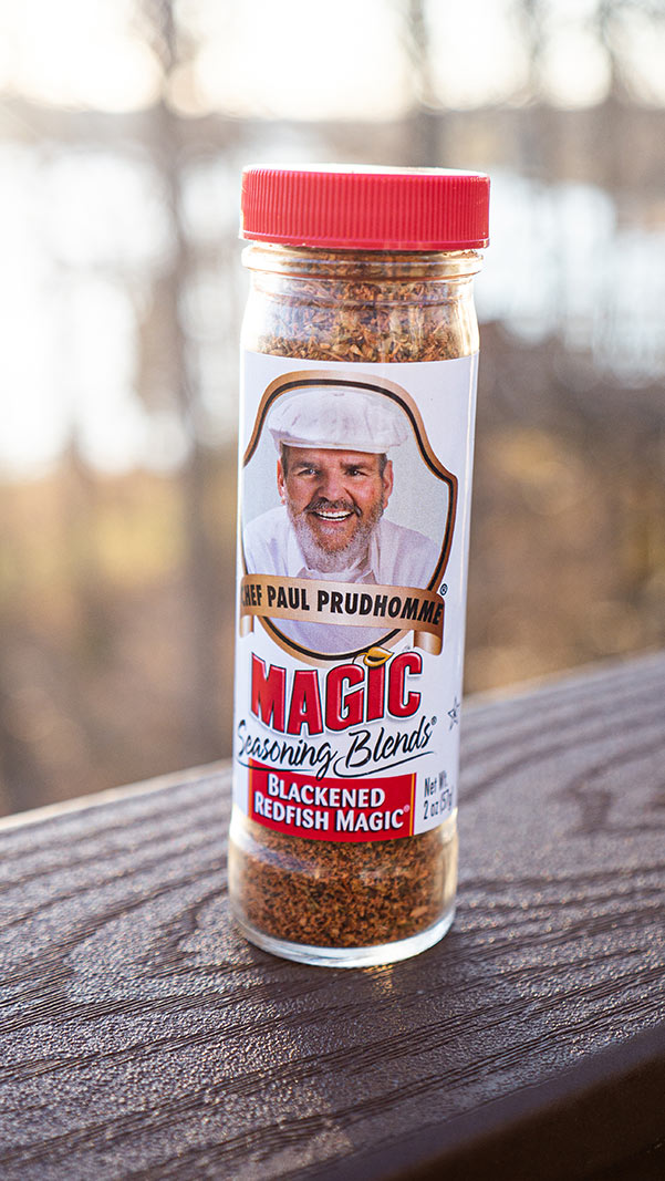 Bottle of Chef Paul Prudhomme's Blackened Redfish Magic sits on a wooden deck