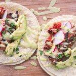 Two Mahi tacos on a cutting board