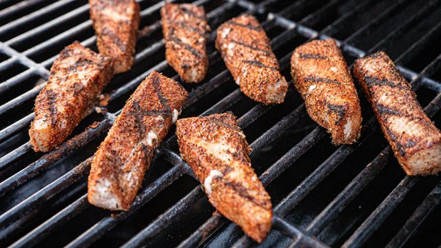 Pieces of seasoned fish cooking on a grill grate