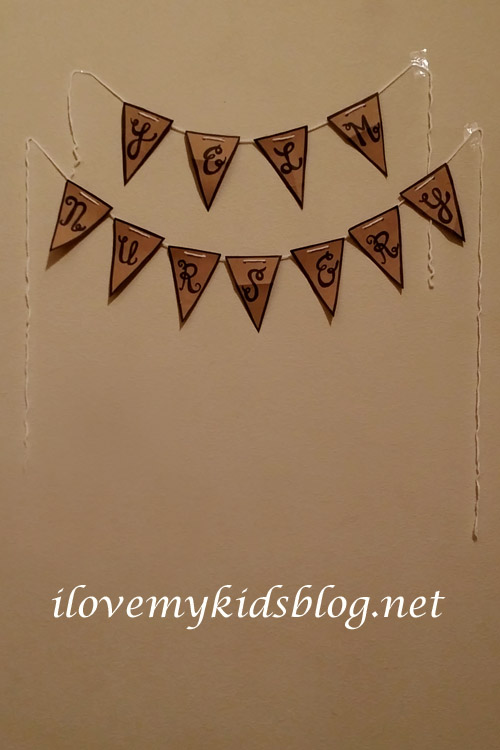 Upcycled Paper Banner with triangle pieces displayed on a wall