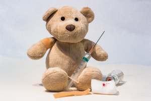 Teddy bear with a syringe and a vaccine