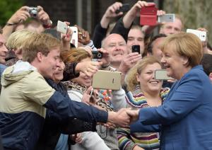 German Chancellor Angela Merkel shakes hands with inhabitants of Duisburg, Germany, when she visits the Duisburg -Marxloh , a neighborhood with a large immigrant population, Tuesday Aug. 25, 2015. (Federico Gambarini/dpa via AP)
