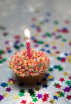 Birthday cupcake on silver paper, with one candle, and sprinkles.