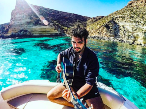 Ignazio playing the guitar on the bow of a boat in the sea at Sicily