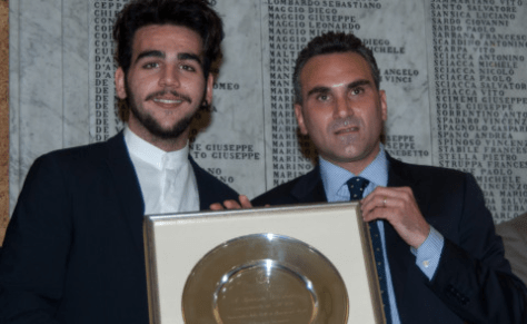 Ignazio being handed a memorial plate with inscription
