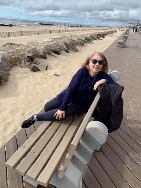 Susan De Bartoli sitting on a bench near the beach