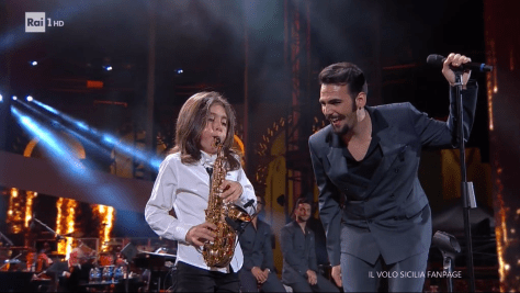 Julian Iorio playing the saxophone with Ignazio smiling at him