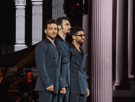Left to right: Closeup of Gianluca, Ignazio and Piero standing on the arena stage with Gianluca looking to his right and smiling at the camera