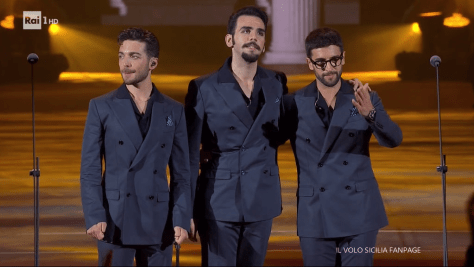 Left to right: Gianluca, Ignazio and Piero embracomg on the arena stage
