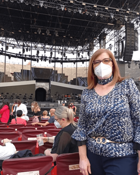 Daniela wearing her mask and standing at her seat in the arena with the stage behind her