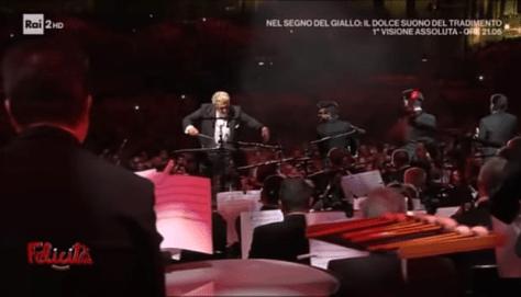 Plácido Domingo conducting the orchestra while IL VOLO sings