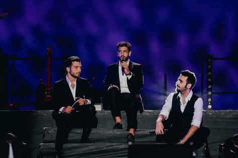 Left to right: Gianluca, Piero and Ignazio sitting and singing on the stage steps