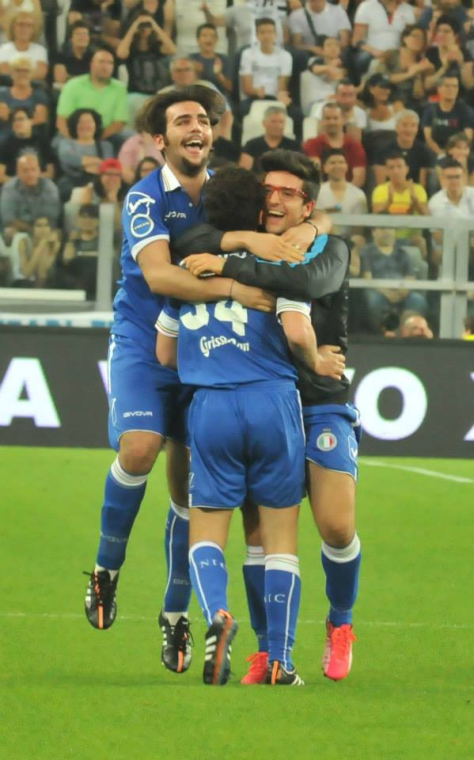 Ignazio, Piero and Gianluca hug on the soccer field after a goal was made.