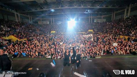 IL VOLO kneeling on state with the audience behind them