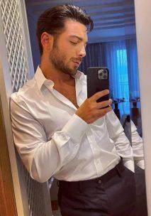 Gianluca in a white long sleeve dress shirt taking a selfie photo