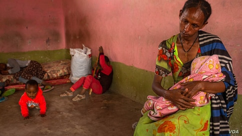 A woman sits with her wounded baby in a central Mekelle, Ethiopia, classroom that was turned into housing for displaced people, June 3, 2021. (VOA/Yan Boechat)