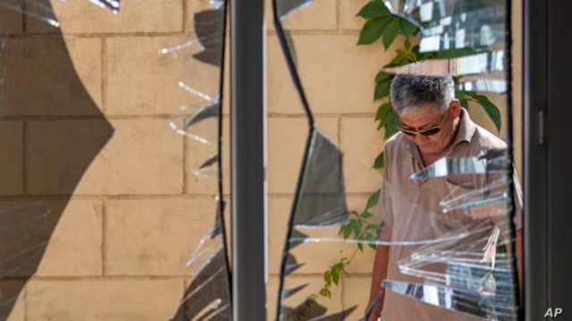 FILE - In this Aug. 30, 2016, file photo, a Chinese Embassy employee examines broken windows at the Chinese Embassy after a…