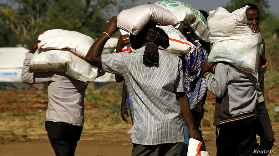 FILE - Ethiopians who fled the ongoing fighting in Tigray region, carry supplies at the Um-Rakoba camp on the Sudan-Ethiopia border, in Kassala state, Sudan, Dec. 17, 2020.