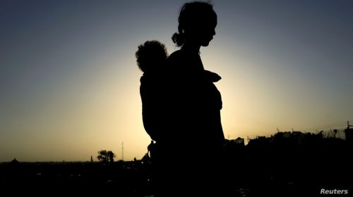 FILE PHOTO: An Ethiopian woman who fled the ongoing fighting in Tigray region, carries her child near the Setit river on the…