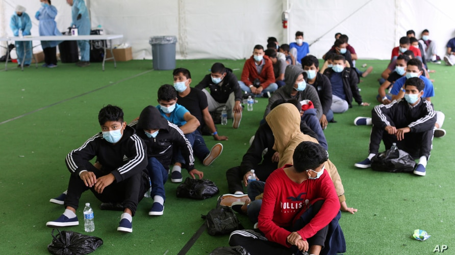 FILE - In this March 30, 2021, file photo, young migrants wait to be tested for COVID-19 at the Donna Department of Homeland…