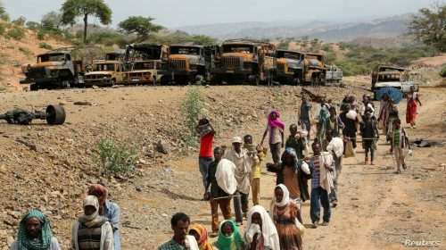 FILE - Villagers return from a market to Yechila town in south central Tigray walking past scores of burned vehicles, in Tigray, Ethiopia, July 10, 2021.