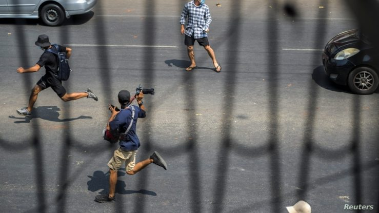 Pro-democracy protesters and a journalist run as riot police officers advance them during a rally against the military coup in Yangon