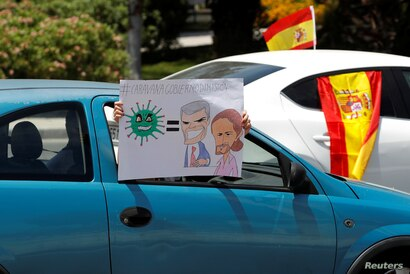A demonstrator holds a sign depicting Spanish Prime Minister Pedro Sanchez and Deputy Prime Minister Pablo Iglesias during a…