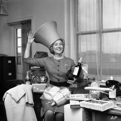 Singing star Vera Lynn tries a lampshade for size as she arranges the many gifts sent to her for the tombola stand she will run…