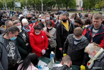 FILE - Supporters of Svetlana Tikhanovskaya collect signatures in support of her nomination as a candidate in the upcoming presidential election, in Minsk, Belarus, May 24, 2020.