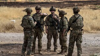 US soldiers stand at an oil field in the countryside of al-Qahtaniyah town in Syria's northeastern Hasakeh province near the…