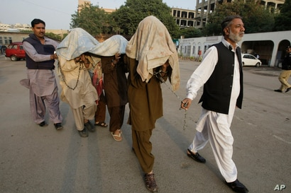 Pakistani security officials escort alleged militants of Tehreek-e-Taliban Pakistan  to anti-terrorist court in Karachi,…