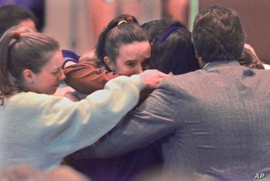 Members of the Columbine High School volleyball team hug the parents of Lauren Townsend, who was killed in the Colombine school shooting, after funeral services for Townsend in Littleton, Colorado, April 26, 1999.