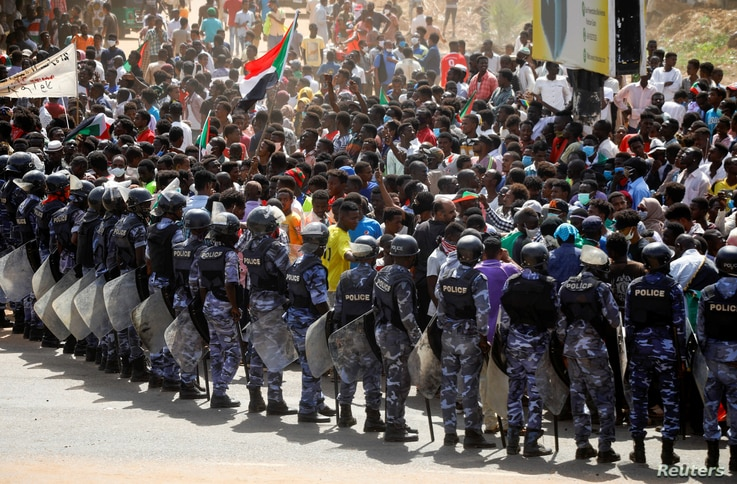 Riot police officers hold position against protesters near the Parliament buildings, as members of Sudanese pro-democracy…