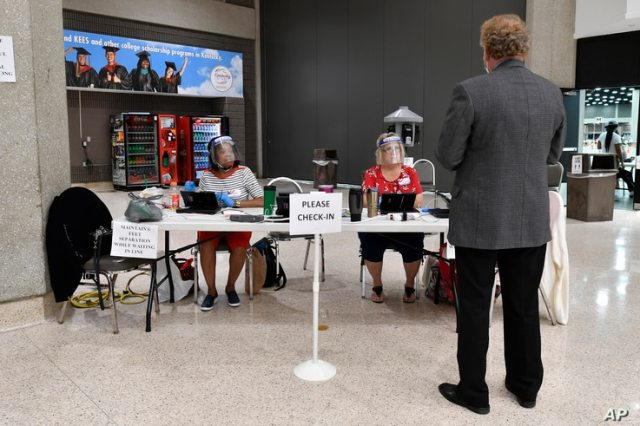 Poll workers wearing face shields assist a voter as he checks in to cast his vote in the Kentucky primary at the Kentucky…