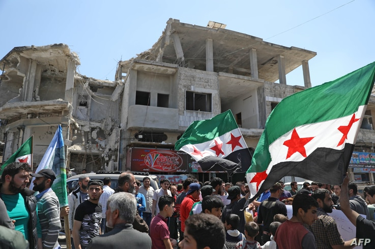 FILE - Syrian demonstrators rally in the town of Binnish in Syria's northwestern Idlib province, May 1, 2020, to condemn a reported attack by the Hayat Tahrir al-Sham group on a protest the previous day.