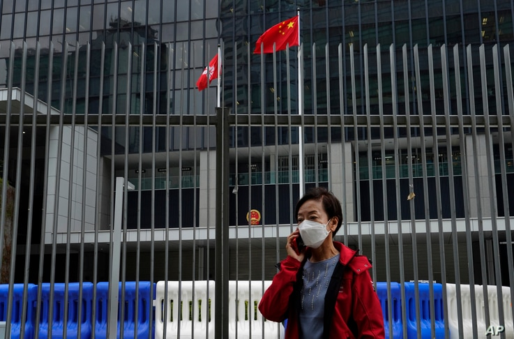 FILE - A woman wearing a protective face mask stands in front of a Chinese national flag and a Hong Kong flag outside government headquarters, in Hong Kong, Feb. 4, 2020.