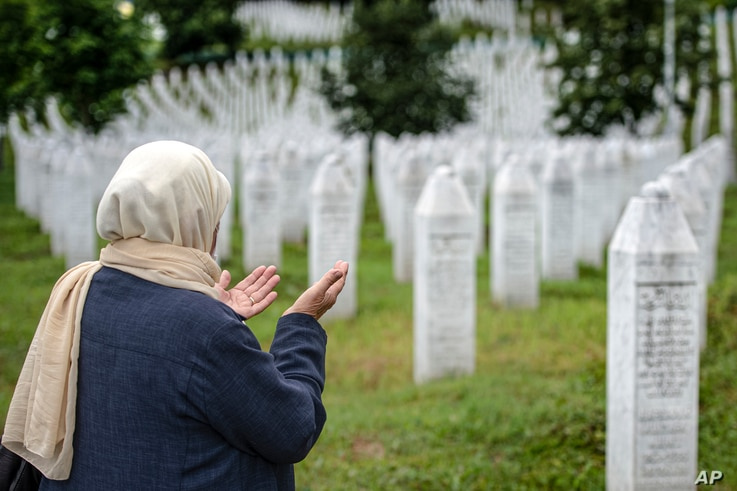 A woman prays at the memorial cemetery in Potocari, near Srebrenica, July 7, 2020. Over 8,000 Bosnian Muslims perished in 10 days of slaughter after the town was overrun by Serb forces in the closing months of the 1992-95 fratricidal war.