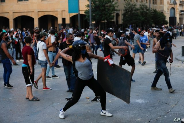 People throw stones during a protest following last week's explosion that killed many and devastated the city, in Beirut, Lebanon, Aug. 11, 2020.