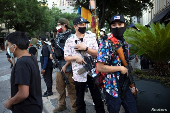 "A Texas Guerrillas member who calls himself, ""Apex,"" third from right, and others carry weapons at a Black Lives Matter rally…"