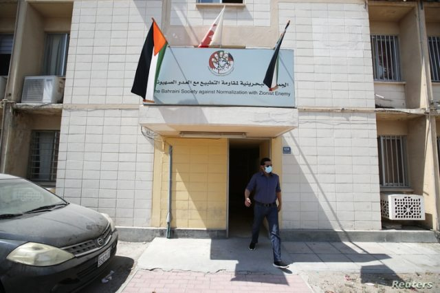 "A man walks out of a building showing an office billboard of ""The Bahraini Society Against Normalization With Zionist Enemy"" in…"