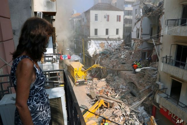 A woman stands on her balcony as she looks at rescuers searching at the site of a collapsed building in Beirut, Lebanon, Friday…