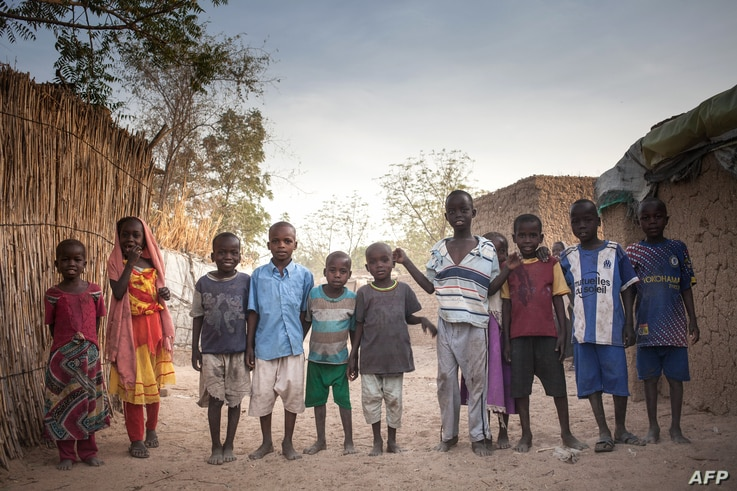 Sudanese refugees children pose for photographs, in the Treguine camp, in Hadjer Hadid, in the Ouadda region of eastern Chad,