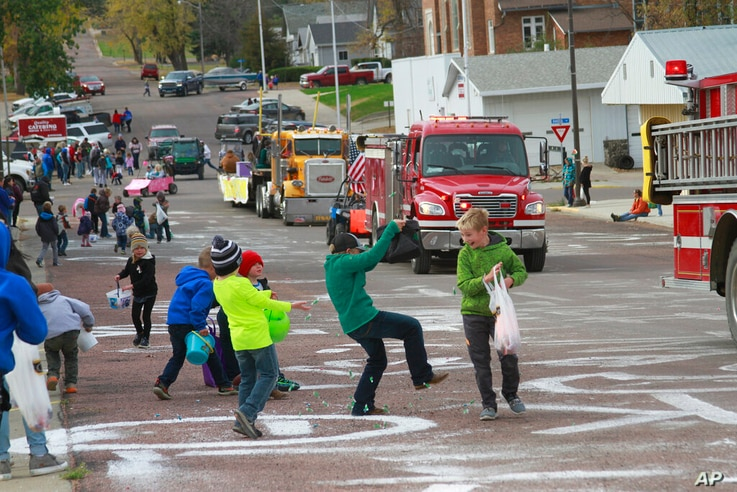 Children scramble for candy during a homecoming parade on Friday Oct. 16, 2020, in Wessington Springs, S.D. The parade had to