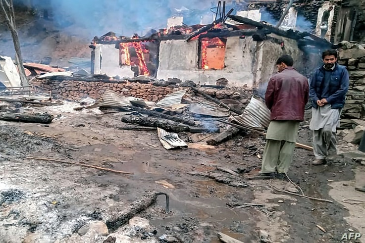Local residents stand beside a burning house following cross border shelling between Pakistani and Indian forces in Tehjain…