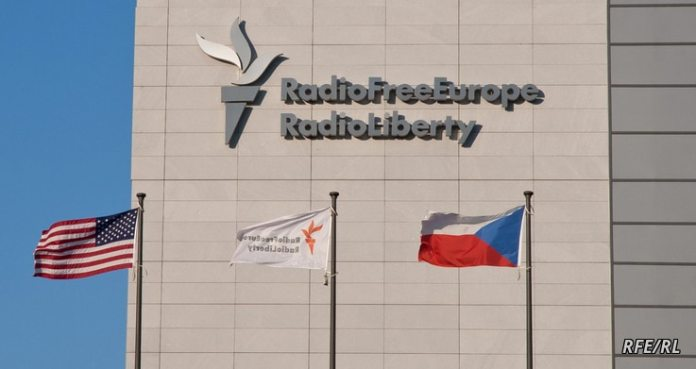 FILE - Movement is seen in the headquarters of Radio Free Europe / Radio Liberty (RFE / RL), with the United States, RFE / RL and the flags of the Czech Republic fluttering in the foreground, in Prague.  (Jan Rambousek - RFE / RL)
